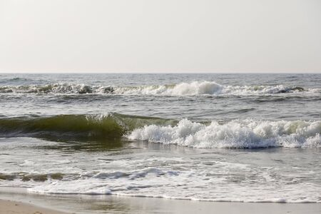 There are waves on the sea waters here at the sandy beach in Kolobrzeg in Poland Stock Photo