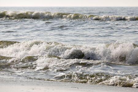 Rapid waves of the Baltic Sea reach the sandy beach in Kolobrzeg in Poland