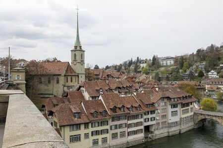 Bern, Switzerland - April 16, 2018: Townhouses of the medieval Old Town are covered with ceramic tiles. There is a church with a tower among the buildings in the immediate vicinity of the river Aare.