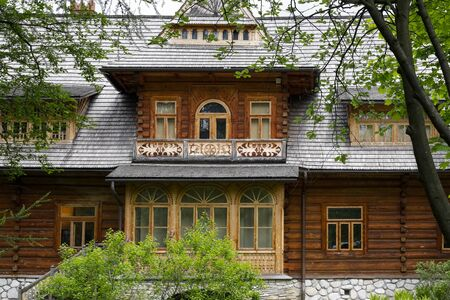 Zakopane, Poland - July 01, 2019: The front elevation of the historic wooden villa, which used to be an ordinary residence, now houses the Tatra Museum. The building is locally called Oksza Villa. Редакционное