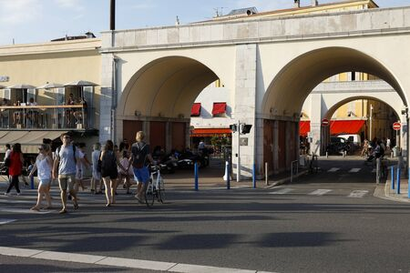 Nice, France - September 17, 2018: Road through the gate that connects the seafront promenade with the famous Cours Saleya street. There are people who cross the street