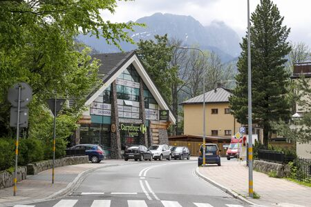 Zakopane, Poland - July 01, 2019: The building with elements of regional architecture houses a shopping centre. In front of the building there are several parked cars.