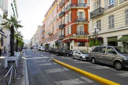 Nice, France - September 20, 2018: Tenement houses and a street where several cars have been parked. The windows of the tenement houses have been equipped with shutters.
