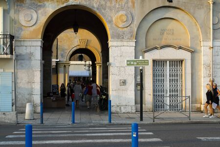 Nice, France - September 20, 2018: On the other side of the street, behind the pedestrian crossing there are two gates, one behind the other. This is the road to the famous street called Cours Saleya.