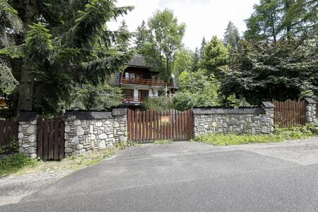 Zakopane, Poland - July 11, 2019: The residential house is seen behind a solid stone fence, there is also a wooden gate. There is a lot of lush vegetation around this building.