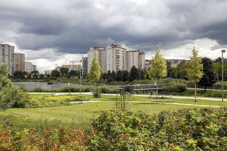 Warsaw, Poland - September 20, 2019: Between the blocks of flats there is a lake, there are also many plants and trees. This is a recreational area of the Goclaw housing estate.