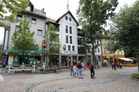 Zakopane, Poland - July 11, 2019: There are tenement houses on Kupowki Street. On the ground floor of these buildings there are shops and restaurants and people walk along the street 에디토리얼
