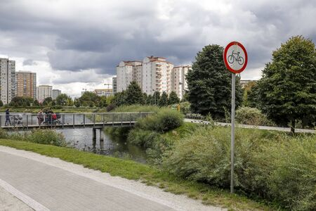Warsaw, Poland - September 20, 2019: The footbridge is over a lake in a residential area called Goclaw. This is a park area near blocks of flats.