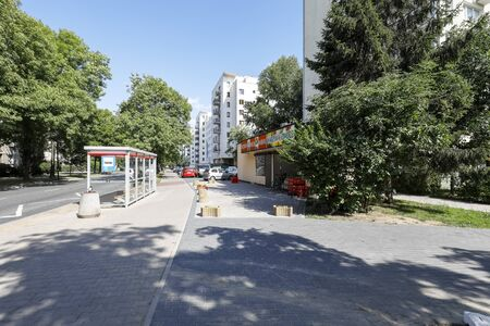 Warsaw, Poland - August 11, 2019: There is a bus stop by the street, there is a grocery store and there are blocks of flats in a housing estate called Saska Kepa. Editöryel