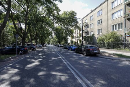Warsaw, Poland - August 11, 2019: Shady street where cars have been parked. Along the street there are many trees and there is a block of flats which are many in this district of Saska Kepa. Editöryel