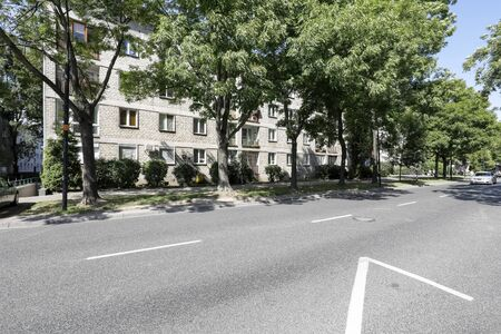Warsaw, Poland - August 11, 2019: There are trees along the wide street and behind them is a block flats that was built for many families in Saska Kepa housing estate. Editöryel