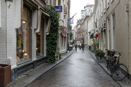 The Hague, The Netherlands - October 11, 2019: Narrow cobbled street in the old part of the city. On both sides of the street there are shops and restaurants and in the distance there are a few people