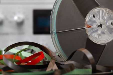 One reel of audio tape (reel to reel) and analog music equipment which can be seen in a background.