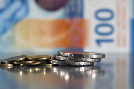 This small pile of several coins has been placed on a flat grey surface and is visible against the background of the blurred 100 Swiss francs note. Banco de Imagens
