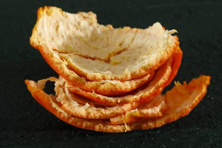 Orange peel of mandarin fruit shown on dark green background.