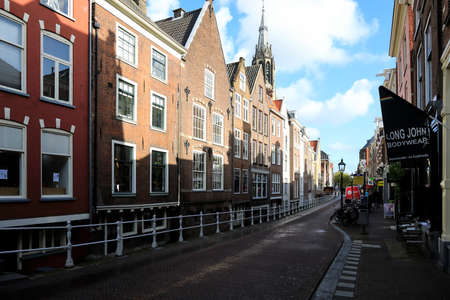 Delft, The Netherlands - October 10, 2019: The city street along which row of stylish houses can be seen. These are old residential buildings.