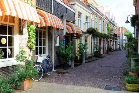 Delft, The Netherlands - October 10, 2019: A row of residential buildings are located by a narrow street. There is a hotel in one of these buildings.