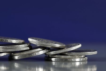 Close up view of Swiss coins which have been stacked on a grey, flat surface and on a dark blue background.
