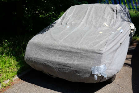 The car has been hidden under the tarpaulin and is now standing on a housing estate street.
