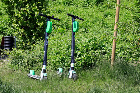 Warsaw, Poland - May 29, 2020: Electric scooters for rent were parked on the grassy ground in the park in Goclaw housing estste. Electric scooters are now a popular means of transport.