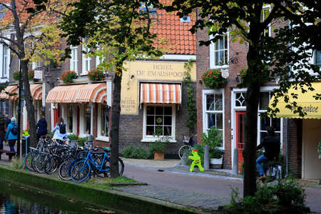 Delft, The Netherlands - October 10, 2019: By the houses in historical part of the city, bikes have been parked at the edge of the canal. 新闻类图片
