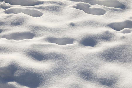 Snow covers the land, on which there are visible boot prints of people who have passed this way before.