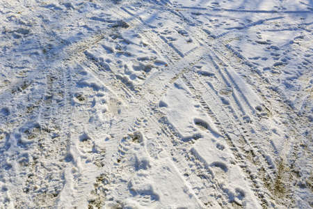 Snow covers the surfaces of the empty parking lot, where you can see traces of the shoes of many people who have walked there before and there are traces of tread.
