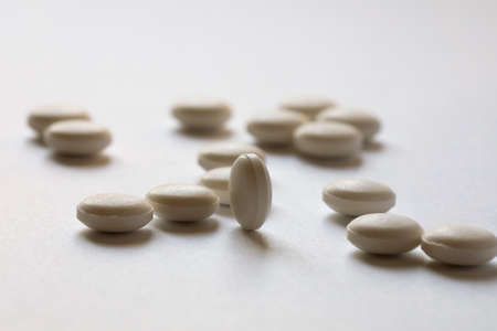 Tablets of identical shape are scattered on the surface of the white paper.