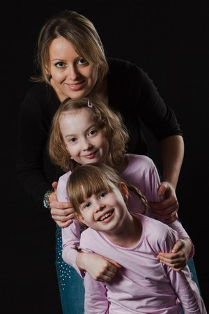 Mother with blond daughters posing on black background. Naturally processed photo with natural look and skin.