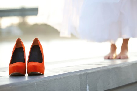 Red-orange wedding shoes in front of barefoot bride. Shallow focus on shoes. Stock Photo