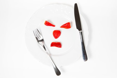 Emoticon make from strawberries saying - mind your body weight before eat- calculate calories. 写真素材