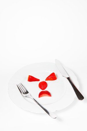 Emoticon make from strawberries saying - mind your body weight - calculate calories before eat.