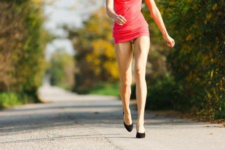Mujer de entrenamiento en vestido rojo corto con piernas trabajadas. Prostituta caminando por la calle con bragas visibles. Foto de archivo