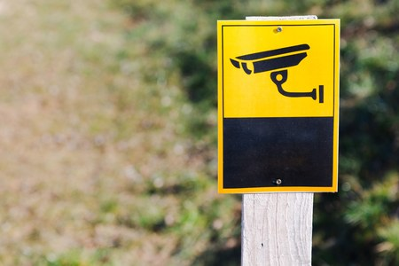 Surveillance camera sign on installed on plain board to protect monitored area.