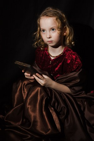 Blond curly baby angel like look. Sitting looking up and holding bible - holy book. Vintage dress in Bordeaux red.