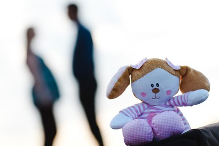 Teddy bear in the foreground and pregnant woman with man in out of focus background.