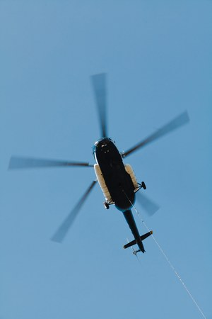 Cargo helicopter with suspended freight on cable. Heavy machinery in action.