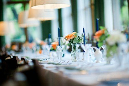 Decorated wedding table in orange, green and blue colors. Shallow focus.