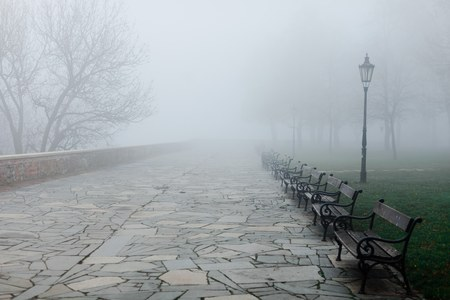 Fogy morning in park, benches disappear in low visibility. Vintage street light in right side.