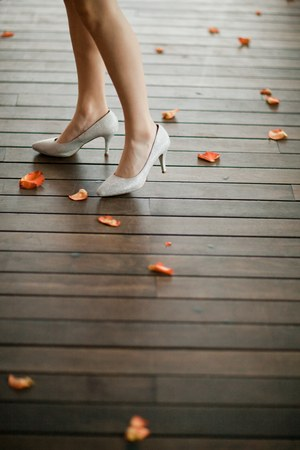 Elegant shoes on heels in silver color on womans leg. Petals fro roses around on wooden floor.