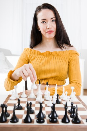 Woman in yellow dress sitting in front of chess planning strategy in business - your move 写真素材