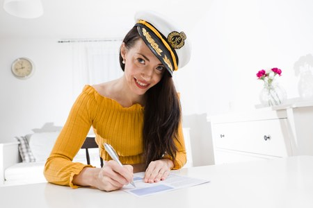 Attractive woman sitting and white table and handwriting with pen wearing captain cap. White background