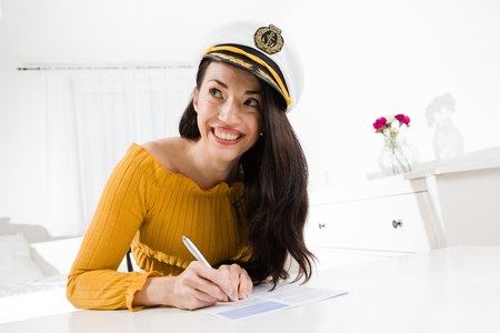 Attractive woman sitting and white table and writing with pen wearing captain cap. Flowers in background Reklamní fotografie