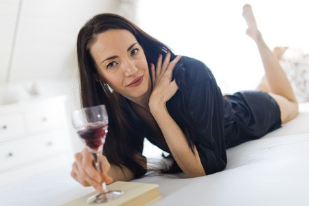 Attractive woman in black sexy sleepwear laying on bed and drinking red wine, bending her legs. Imagens