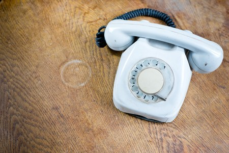 Old white cable telephone on old table surface. Communication technology from 80s - concept 版權商用圖片