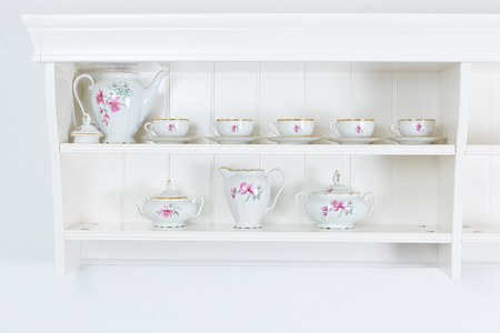 White tea shelf with mugs.Tea dish on the white wall, free space for text or highlights - concept