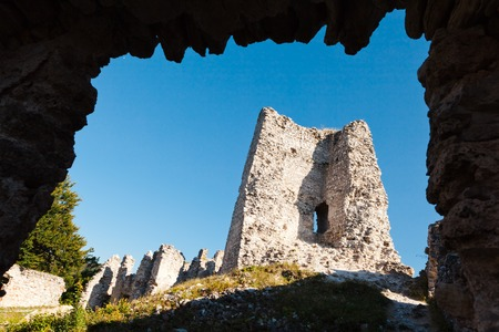 View on ruined walls of old medieval castle. Framed naturally with rocks of entering gate.