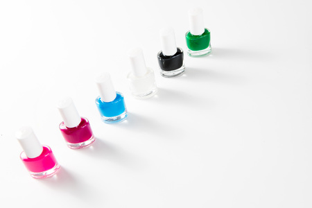 Sets of nail polishes in many colors for girls - shallow focus on white background - diagonal composition