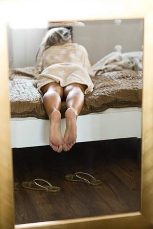 Woman's legs in mirror framed in golden frame, lying barefoot on bed
