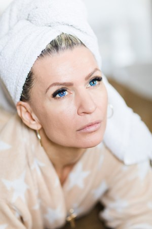 Attractive woman with blue eyes with towel on head after relaxation in bedroom.
